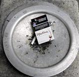 <p>A discarded cigarette pack lies in an ashtray outside an office tower in downtown Toronto February 19, 2007. REUTERS/J.P. Moczulski</p>