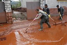 <p>Люди расчищают улицу от токсичных отходов в городе Девечер 5 октября 2010 года. Венгерское правительство объявило во вторник чрезвычайное положение в трех областях на западе страны после разлива токсичных отходов, жертвами которого уже стали как минимум три человека. REUTERS/Bernadett Szabo</p>