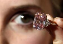 <p>An employee poses with a 24.78 carat Fancy Intense Pink diamond at Sotheby's in London October 25, 2010. REUTERS/Luke MacGregor</p>