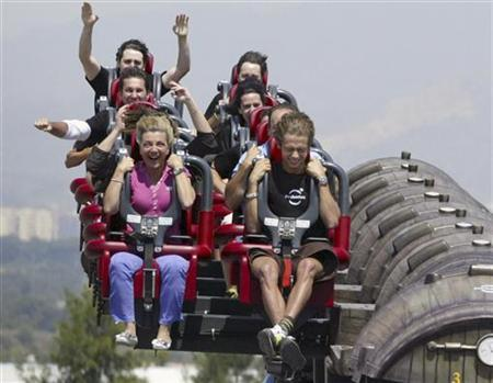 MotoGP rider Valentino Rossi (R) rides the new roller coaster attraction ''Furius Baco'' at Port Aventura amusement park in Salou, near Barcelona, June 7, 2007. REUTERS/Bea Martinez