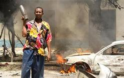 <p>Мужчина держит несработавший снаряд на месте взрыва заминированной машины в столице Сомали Могадишо 15 февраля 2010 года. Сомали сменила Ирак на первом месте рейтинга стран с наибольшим риском террористической угрозы, а Россия поднялась 10-ю строчку, расположившись по соседству с Йеменом, свидетельствуют данные компании Maplecroft. REUTERS/Mowlid Abdi</p>