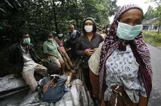 <p>Villagers wearing masks stand on a street after fleeing from their village in Sidorejo in Klaten of the Indonesia central Java province November 3, 2010. REUTERS/Andry Prasetyo</p>