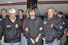 <p>Подозреваемый в торговле оружием россиянин Виктор Бут (в центре) в аэропорту в Нью-Йорке, 16 ноября 2010 года. Гражданин России Виктор Бут был доставлен во вторник в США, где ему будут предъявлены обвинения в торговле оружием, сообщило министерство юстиции США. REUTERS/U.S. Department of Justice/Handout</p>
