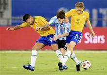 <p>Argentino Lionel Messi recebe marcação de André Santos e Lucas no amistoso contra o Brasil em Doha, no Catar. 17/11/2010 REUTERS/Mohammed Dabbous</p>