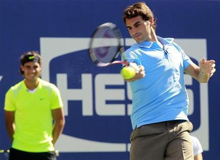 Roger Federer (R) of Switzerland hits a shot at a target in a skills competition as Rafael Nadal of Spain looks on during the Arthur Ashe Kids Day at the U.S. Open tennis tournament in New York, August 28, 2010. REUTERS/Brendan McDermid