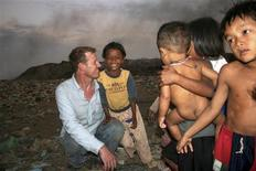 <p>Former Hollywood film executive Scott Neeson is seen with local children who scavenge at the Steung Meanchey trash dump outside Phnom Penh, Cambodia, in this January 2007 photo provided by the subject to Reuters on November 19, 2010. REUTERS/Norman Neeson/Handout</p>