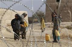 <p>Afghan children look from behind a razor wire at an outpost in Zhari district in Kandahar Province, Afghanistan November 20, 2010. REUTERS/Peter Andrews</p>