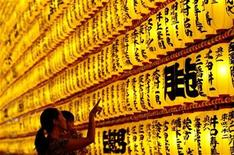 <p>A family looks at paper lanterns during the Mitama Festival at Yasukuni Shrine in Tokyo July 13, 2007. REUTERS/Issei Kato</p>