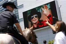 <p>A fan points at a monitor revealing a picture of Michael Jackson as a mounted police officer looks on outside the Staples Center following a memorial service for Jackson in Los Angeles July 7, 2009. REUTERS/Joshua Lott</p>