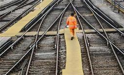 <p>A worker crosses train tracks at Clapham Junction in London March 25, 2010. REUTERS/Luke MacGregor</p>