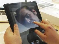 <p>A shopworker is reflected in the screen of an iPad tablet computer at an Apple store while demonstrating the device during its UK launch in central London May 28, 2010. REUTERS/Luke MacGregor</p>