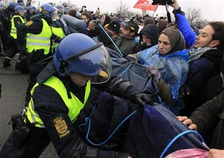 Danish riot police officers struggle with protesters of ''Reclaim Power'' that tried to set up a road blockade with air mats outside the conference center in Copenhagen, where world leaders have gathered for the United Nations Climate Change Conference December 16, 2009. REUTERS/Pawel Kopczynski