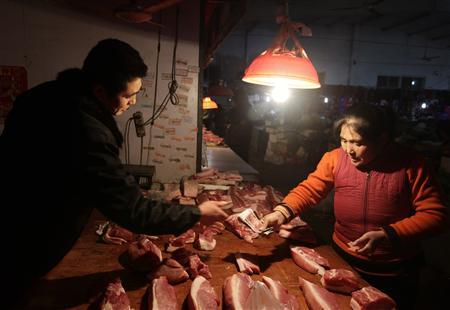 A woman pays for pork at a market on the outskirts of Beijing, December 27, 2010. China made fresh assurances that it will keep inflation in check, saying it will improve efforts to stabilise prices and ensure an abundant supply of essential commodities ahead of the Chinese New Year. REUTERS/Jason Lee