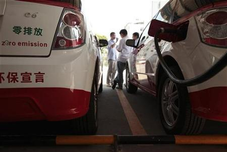 A BYD E6 electric car, used as a taxi in Shenzhen (R), is plugged in to charge at a taxi company's car park in the southern Chinese city of Shenzhen May 24, 2010. REUTERS/Tyrone Siu