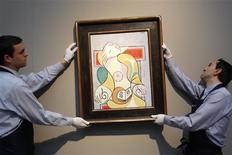 """<p>Sotheby's art handlers hold the painting """"La Lecture"""" by artist Pablo Picasso (1881-1973) at Sotheby's auction house in Paris January 19, 2011. REUTERS/Benoit Tessier</p>"""