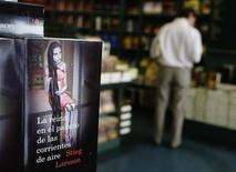 "<p>A customer reads a copy of Swedish author Stieg Larsson's latest book in his Millennium series of crime novel, ""The Girl Who Kicked the Hornets' Nest"", at a Madrid bookstore June 18, 2009. REUTERS/Susana Vera</p>"