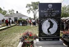 <p>People gather outside the childhood home of pop star Michael Jackson in Gary, Indiana June 25, 2010. REUTERS/John Gress</p>
