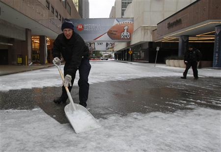 A hotel employee shovels snow from a street in front of a hotel housing news media after a storm front moved through Dallas, Texas, February 1, 2011. REUTERS/Brian Snyder