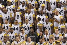 <p>Pittsburgh Steelers head coach Mike Tomlin (center) sits quietly as his team jokes around during their team photo shoot following media day for Super Bowl XLV at Cowboys Stadium in Arlington, Texas, February 1, 2011. REUTERS/Brian Snyder</p>