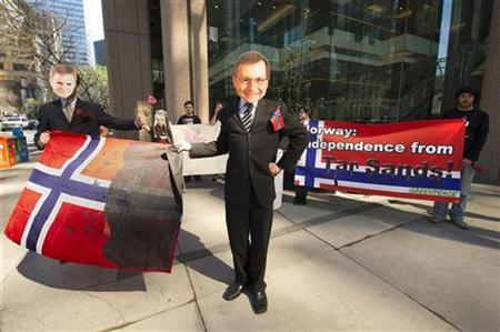 Greenpeace protesters dressed as Statoil Chief Executive officer Helge Lund (L) and Alberta Premier Ed Stelmach hold a Norweigien flag dipped in oil outside the offices of Statoil Canada in Calgary, Alberta, May 17, 2010. REUTERS/Todd Korol