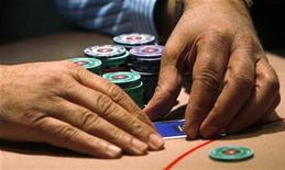 <p>A contestant covers his cards during a poker tournament in London, October 1, 2008. REUTERS/Suzanne Plunkett</p>