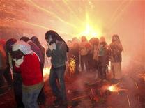 """<p>People get hit by firecrackers during the Yanshui Beehive Rockets Festival, as part of the Chinese Lantern Festival or """"Yuan Xiao Jie"""", in Tainan County February 16, 2011. REUTERS/Stringer</p>"""