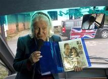 <p>Tour guide Charmian Griffiths holds up a magazine clipping of Britain's Prince William and his fiancee Kate Middleton during a bus tour highlighting areas of Berkshire where Middleton grew up, in Bradfield February 20, 2011. REUTERS/Kieran Doherty</p>