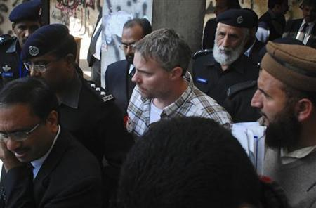 A U.S. consulate employee is escorted by police and officials out of court after facing a judge in Lahore, January 28, 2011. REUTERS/Tariq Saeed