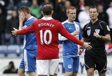<p>Wayne Rooney do Manchester United gesticula para o árbitro Mark Clattenburg após o choque com James McCarthy do Wigan Athletics, durante a partida da primeira liga inglesa em Wigan, em 26 de fevereiro de 2011. REUTERS/Phil Noble</p>