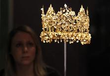 "<p>A museum employee poses for photographers behind a gold crown circa first century AD, from Tillya Tepe, during a preview of the exhibition ""Afghanistan: Crossroads of the Ancient World"" at the British Museum in London March 1, 2011. The exhibition, which displays precious and unique pieces on loan from the National Museum of Afghanistan in Kabul, opens on March 3 and runs until July 3. REUTERS/Suzanne Plunkett</p>"