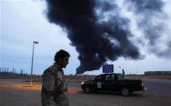 <p>Солдат из преданных Мауммару Каддафи частей у КПП на фоне горящего нефтехранилища в Рас-Лануфе 12 марта 2011 года. Силы лидера Ливии Муаммара Каддафи нанесли бомбовый удар по имеющему стратегическое значение нефтяному порту Марса-эль-Брега на востоке страны и выбили оттуда повстанцев. REUTERS/Chris Helgren</p>