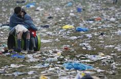 <p>A couple kisses at dawn in a field of litter at the Glastonbury Festival 2008 in Somerset in southwest England June 29, 2008. REUTERS/Luke MacGregor</p>