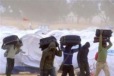 <p>Somalian refugees who fled the unrest in Libya walk in a refugee camp near the Libyan and Tunisian border crossing of Ras Jdir March 15, 2011. REUTERS/Anis Mili</p>