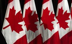 <p>Canadian Prime Minister Stephen Harper's shadow is cast on flags while holding a news conference in Surrey, British Columbia March 15, 2011. REUTERS/Andy Clark</p>
