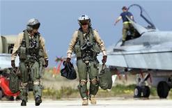 <p>Канадские пилоты идут по территории военной базы НАТО на Сицилии, 24 марта 2011 года. Организация Североатлантического договора (НАТО) пообещала обеспечить соблюдение бесполетной зоны над охваченной народными волнениями Ливией, но пока не взяла на себя управление одобренной ООН военной операцией в богатой нефтью североафриканской стране, где уже более 40 лет правит Муаммар Каддафи. REUTERS/Tony Gentile</p>