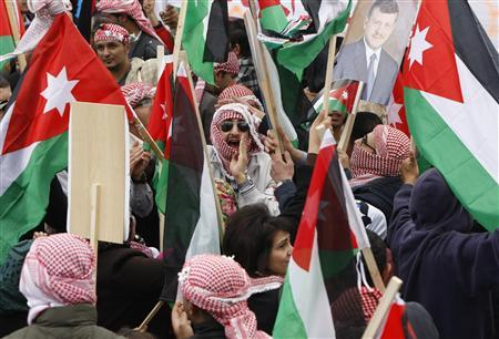 Supporters of Jordan's King Abdullah wave the national flags and carry pictures of the King during a demonstration in his support in Amman March 25, 2011. REUTERS/Ali Jarekji