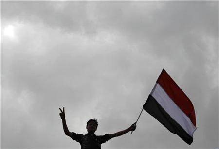 An anti-government protester waves the Yemen national flag during a rally to demand the ouster of Yemen's President Ali Abdullah Saleh outside Sanaa University March 25, 2011. REUTERS/Ammar Awad