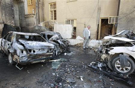 A resident inspects damaged vehicles at the site of a bomb attack in Baghdad, March 29, 2011. Two Katyusha rockets landed near a hotel on Abu Nawas Street in central Baghdad and wounded two people, an Interior Ministry source said. REUTERS/Mohammed Ameen