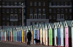 <p>A man walks his dog past beach huts, in Brighton southern England March 7, 2011. REUTERS/Luke MacGregor</p>
