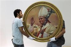 "<p>Workers hold a painting of the late pope John Paul II during the staging of the exhibition ""Karol Josef Wojtyla"" at the Villacero exhibition hall in Monterrey, April 22, 2010. REUTERS/Tomas Bravo</p>"