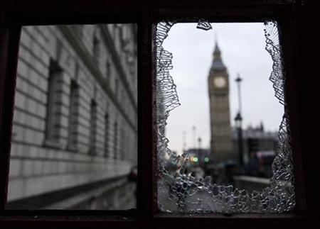 The Big Ben clock tower is seen through the broken window of a damaged telephone box after a protest in Westminster, in central London December 10, 2010. REUTERS/Stefan Wermuth