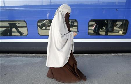 Kenza Drider, a French Muslim of North African descent, wearing a niqab, walks on a platform as she arrives at the Gare de Lyon railway station in Paris April 11, 2011. REUTERS/Jean-Paul Pelissier
