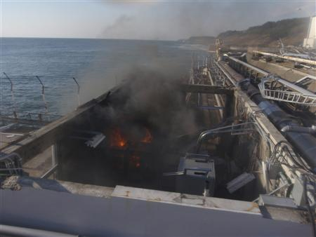 Fire and smoke are seen at a building for sampling from seawater near No.4 reactor of the Fukushima Daiichi Nuclear Power Plant, April 12, 2011. REUTERS/Tokyo Electric Power Co.