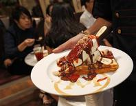 <p>A waitress carries a plate of ice-cream for a customer in Magnum's cafe in Jakarta's mall April 14, 2011. REUTERS/Supri</p>