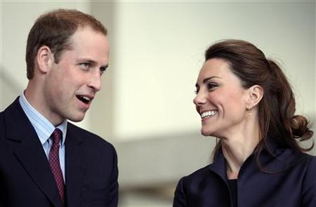 Britain's Prince William speaks, watched by his fiancee Kate Middleton at the Darwen Aldridge Community Academy (DACA), in Darwen, northern England April 11, 2011. REUTERS/Adrian Dennis/Pool