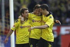 <p>Kevin Grosskreutz do Borussia Dortmund, Robert Lewandowski e Mario Goetze comemoram gol contra o Freiburg no Campeonato Alemão. O Dortmund arrancou para conquistar seu primeiro campeonato alemão desde 2002, ao vencer por 3 x 0 no domingo e abrir uma vantagem de oito pontos na liderança. 17/04/2011 REUTERS/Ina Fassbender</p>