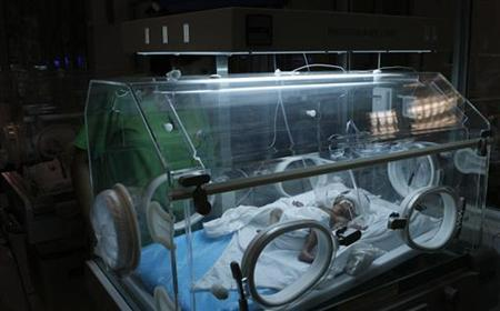 A nurse looks at a prematurely born baby lying inside a phototherapy unit at a hospital in Hanoi August 13, 2009. REUTERS/Kham