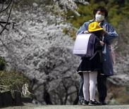 <p>New student Rika Kikuchi has her new school hat put on by her grandmother after an entrance ceremony at Kamaishi elementary school in Kamaishi, Iwate prefecture, after the area was devastated by the March 11 earthquake and tsunami, April 20, 2011. REUTERS/Toru Hanai</p>