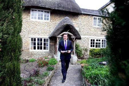 Britain's Prime Minister David Cameron delivers leaflets while campaigning against adoption of the alternative vote (AV) in Eynsham, Oxfordshire April 15, 2011. REUTERS/Steve Parsons/POOL