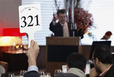 Auctioneer John Kapon, president and director of auctions for Acker Merrall & Condit, takes bids from people at the restaurant Marea and bidders online at a rare wine auction in New York March 19, 2011. REUTERS/ Mark Dye